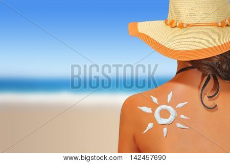 Woman with sun shaped sunscreen on her back. Sun protection concept. Summer time on the beach