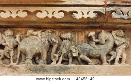 Procession of indian people elephants and horses on stone textures wall of Khajuraho temple India. UNESCO Heritage site built between 950 and 1150 in India belong to Hinduism and Jainism.