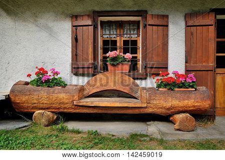 Alpine traditional facade house with bench, landscape design