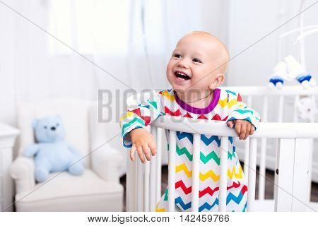 Cute laughing baby standing in bed after nap time. Nursery interior for young kids. Adorable little boy playing in his crib. White furniture for children bedroom. poster
