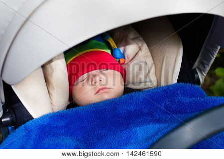 Cute little baby in funny colorful hat sleeping in infant car seat on a walk in a park