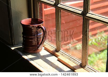 Big brown clay cup with handle set on window sill, with sunlight streaming through