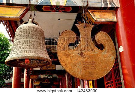 Dan Jing Shan China - November 16 2012: A traditional temple bell and hanging gong inscribed with Chinese characters hang from a pavilion at the Fo Shan Gu Xi Buddhist Temple