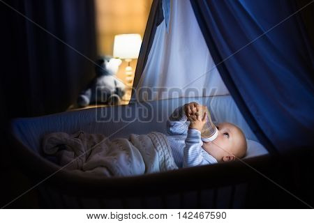 Adorable baby drinking milk in blue bassinet with canopy at night. Little boy in pajamas with formula bottle getting ready to sleep in dark room with crib lamp and toy bear. Bed time drink for kids.