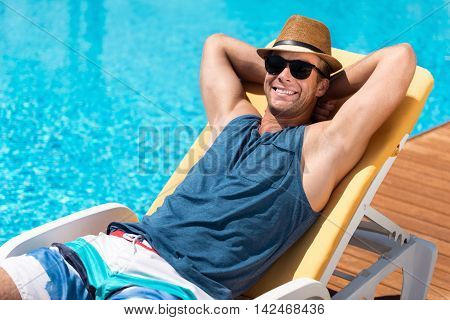 Endless summer . Handsome positive delighted man lying on the sunbed and resting near pool while sun bathing