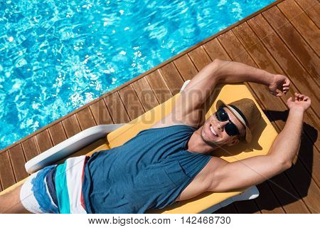Beloved rest. Top view of content joyful handsome man lying on the sun bed and smiling while resting near swimming pool