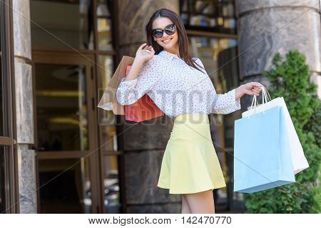 Joyful young woman is shopping in city. She is standing outdoors and holding packets. Lady is smiling