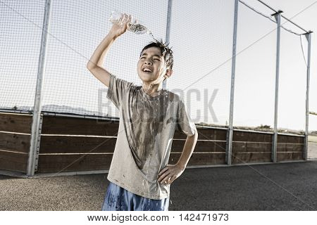 Boy cools off with water over his head.