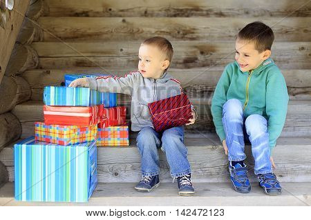 kids rejoice to gifts. two cute boys sitting on the steps with gifts and look forward to unwrapping presents. the concept of happy holidays