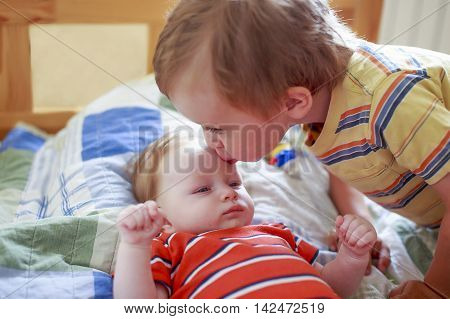 little boy kissing his newborn sister. toddler tenderly kissing the forehead his younger sister. the concept of love and friendship between siblings