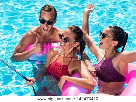 Involved in jubilation. Cheerful delighted smiling friends using inflatable rings and having fun in a swimming pool while making selfies