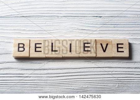 BELIEVE word written on wood block. Wooden ABC