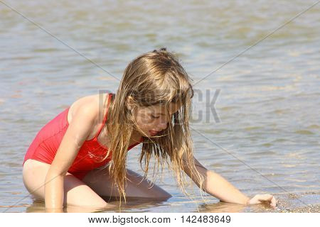 Blonde girl looking for a treasure on the beach