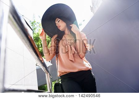Low angle of attractive girl posing on balcony. She is touching sunhat and looking forward with anticipation
