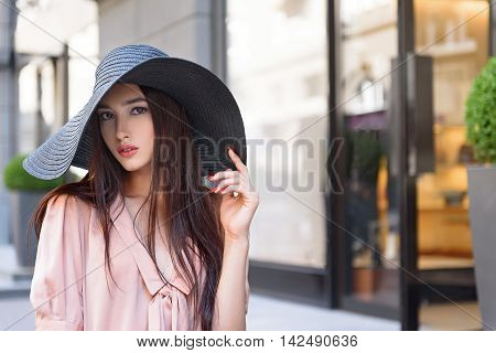 Attractive girl is resting in city. She is standing in big sunhat and looking at camera with confidence