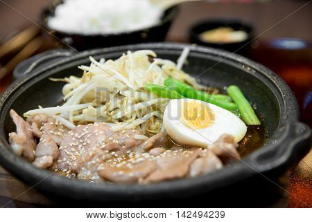 Korean spicy bbq pork served on a hot plate with side dishes and rice. Korean traditional food.