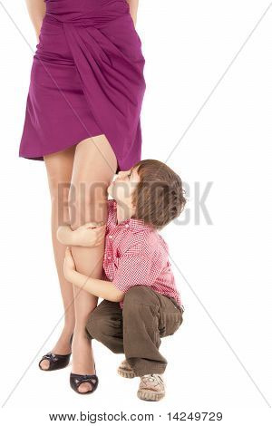 Little Boy Hugging The Leg Of His Mum