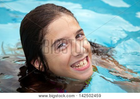 A happy tween girl in a swimming pool smiles with crooked teeth. Her lips and gums are slightly blue because she is cold.