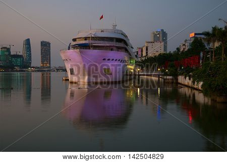DANANG, VIETNAM - JANUARY 05, 2016: Boat from the city promenade in the evening twilight. Tourist terminal