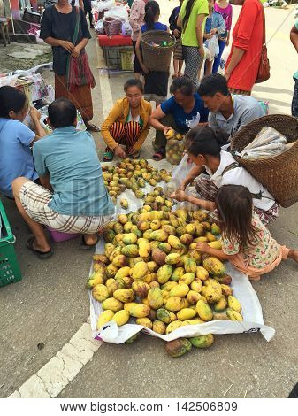 CHIANG RAI THAILAND - AUGUST 9 : vertical photo of unidentified people buying mangoes in a market at the Thai-Laos frontier on August 9 2016 in Chiang rai Thailand. This is one of travel attraction in Chiang Rai.