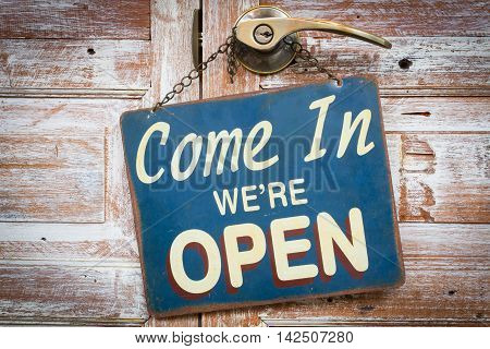 Come In We're Open on the wooden door retro vintage style