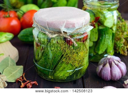 Pickled cucumbers in glass jars. Spices and vegetables for preparation of pickles.