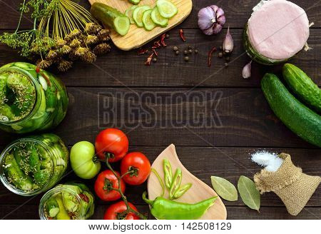 Pickled cucumbers in glass jars. Spices and vegetables for preparation of pickles. top view