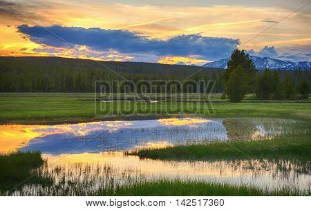 Beautiful vivid sunset at Yellowstone National Park. Mountains and sky is reflecting in a lake. Wyoming, USA