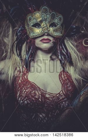 Blonde with gold mask on red cloth embroidered golden thread, mystery and sensuality