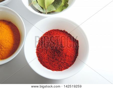 Spices in white bowls, chili poser, curry and laurel leaves, isolated on white background. Food ingredients.