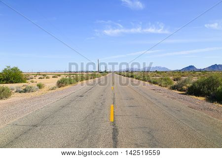 Road through the Sonoran Desert Arizona USA with overhead power cables to one side of the road in the back a settlement and a mountain range.