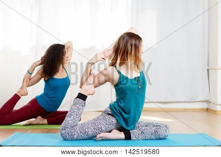 Two slender flexible young woman doing yoga pigeon pose kapotasana in fitness studio
