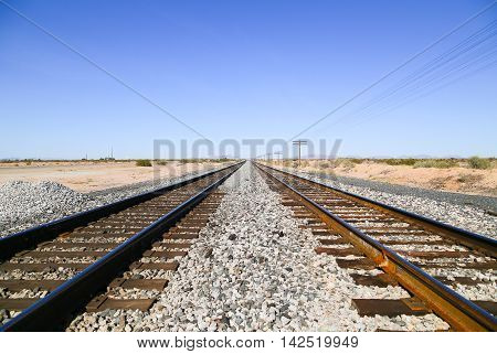 Railroad tracks in the Sonoran Desert Arizona USA with overhead power cables to one side and the Old US Highway 80 to the other and a mountain range in the back.