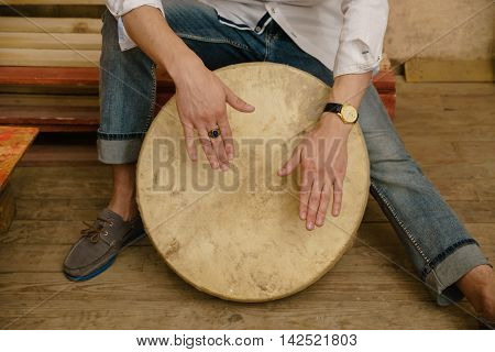 A close up picture of man's hands playing a tambourine