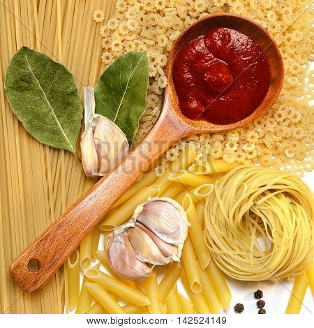 A variety of pastas, a wooden spoon of tomato ketchup and spices, top view.