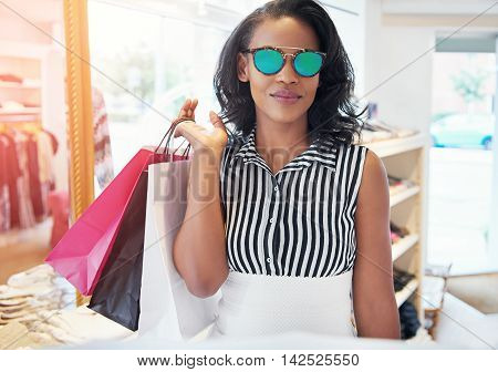 Trendy stylish young woman shopping in sunglasses standing in a fashion boutique with her purchases in bags over her shoulder