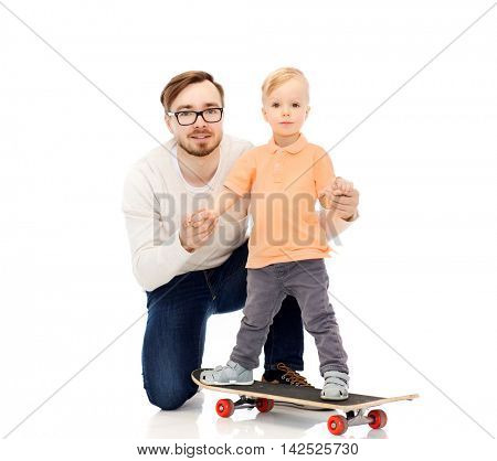 family, childhood, fatherhood, leisure and people concept - happy father and and little son on skateboard