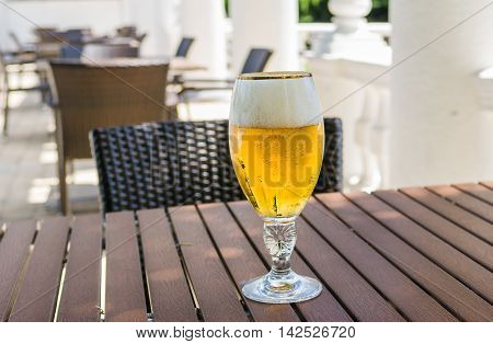 Glass of beer in empty cafe is waiting for the first visitor.