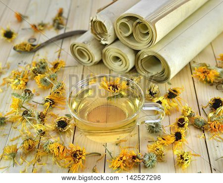 Homeopathic medicine and healthcare still life with dried calendula flowers, glass cup of herbal tea and paper scrolls on wooden planks background