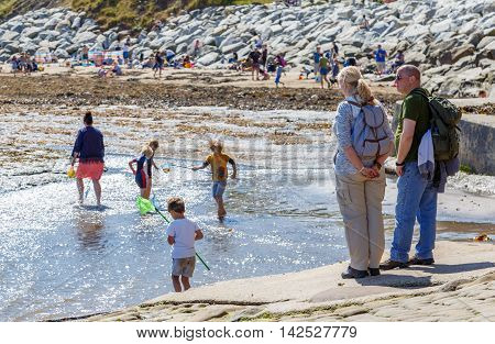 ROBIN HOODS BAY ENGLAND - AUGUST 12: Adult man and woman look on as various people and children play in the sea. In Robin Hoods Bay North Yorkshire England. On 12th August 2016.