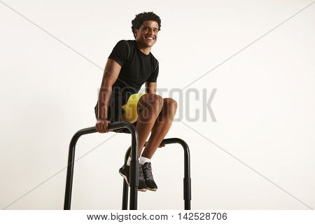 Strong Young Black Athlete Rising Knees On Parallel Bars