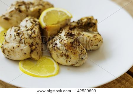 White chicken meat with lemon and herbs served on a white plate. Low fat and low carbs diet. Healthy eating concept