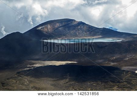 Crater in the mountains with a lake on a cloudy day