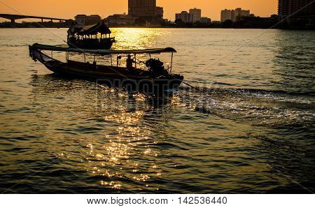 Silhouette of Long tail boat in the Chao Phraya river at Sunset time