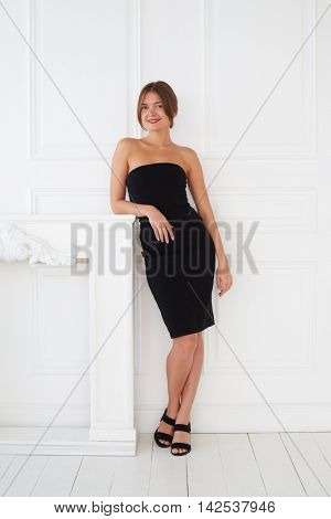 An elegant ladylike girl with red lips and in a small black dress has a photo session in the photo studio