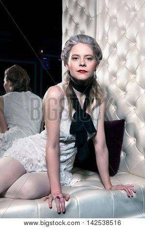 Blonde girl is sitting on a sofa in the boudoir Modern interpretation of Marie Antoinette
