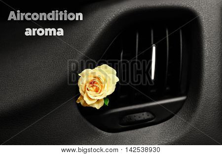 Rose in car air vent with text aircondition aroma on dashboard. Air conditioning concept.