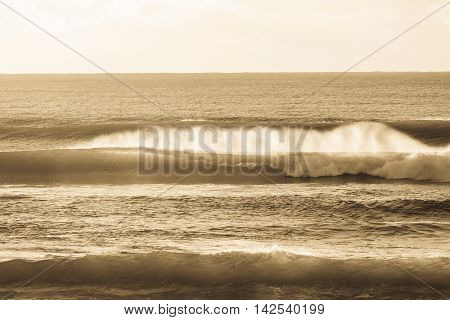Waves crashing ocean water towards beach coastline in vintage sepia antique.
