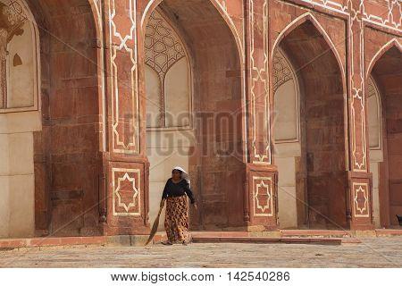 DELHI INDIA - NOVEMBER 4: Unidentified woman sweeps at Humayun's Tomb on November 4 2014 in Delhi India. Humayun's Tomb was the first garden-tomb on the Indian subcontinent.