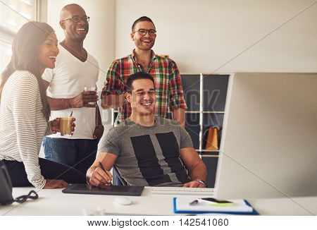 Casually dressed laughing men and woman holding drinks around computer with stylus and tablet on desk in office